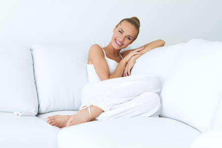 Young beautiful woman sitting on couch at her room Stock Photo - 13201957