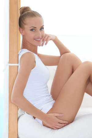 shapely legs: Beautiful elegant blonde woman with her hair in a bun relaxing on a cushioned seat in panties and a shirt