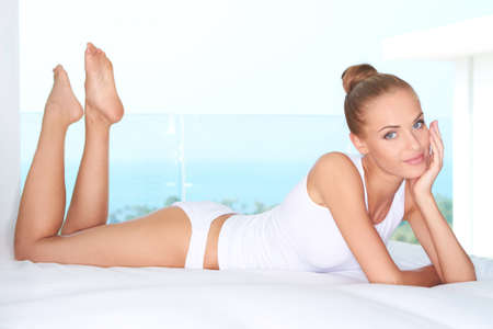 lying on stomach: Beautiful woman lying on white bed at modern luxury room Stock Photo