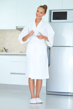 Elegant smiling woman in white robe standing in front of a fridge drinking an early morning cup of coffee Stock Photo - 13202115
