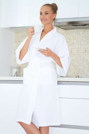 Smiling woman standing in a white bath robe enjoying a cup of coffee photo