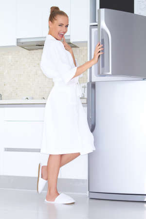 lady slipper: Vivacious woman in a white bathrobe and slippers standing laughing as she opens the freezer unit of her refrigerator