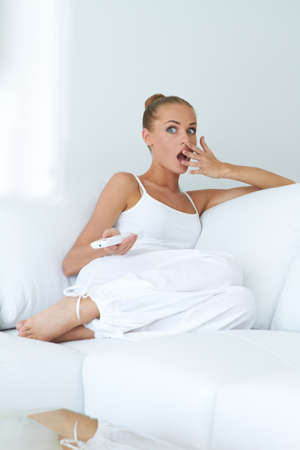Young woman is in shock while watching tv on sofa photo