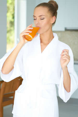 Woman in a white bath robe with her eyes closed enjoying a large glass of fresh orange juice in the morning for breakfast photo