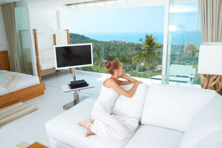 airy: A beautiful woman relaxes on a white sofa in a modern airy bright living-room enjoying the luxury of a tropical lifestyle