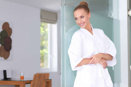 Beautiful woman standing in white bathrobe in modern room Stock Photo - 13202179