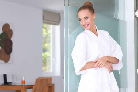 Beautiful woman standing in white bathrobe in modern room Stock Photo - 13202179