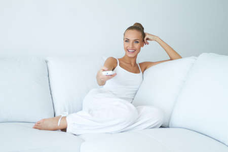 Happy young woman watching tv on sofa photo