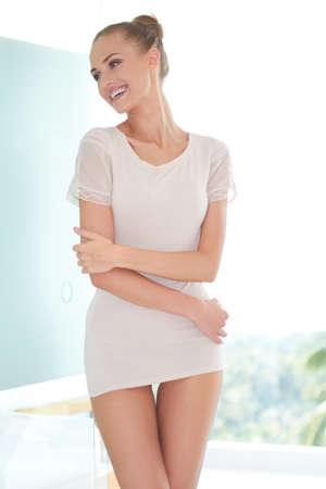 high key: Bella donna sensuale in minigonna molto breve posa laterale per macchina fotografica in un contesto high key Archivio Fotografico