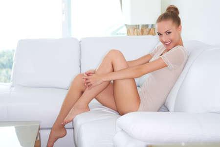 benen: Zijaanzicht van mooie introspectieve vrouw in krappe outfit zittend op een witte bank met haar blote voeten op de salontafel