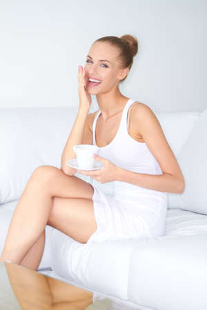Gorgeous woman with a beautiful smile sitting cross legged on a white sofa drinking coffee Stock Photo - 13201770