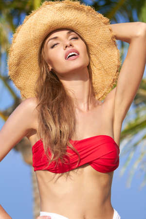tantalising: Beautiful woman in straw hat and bikini with her head tilted back ,  her lips parted and her eyes closed