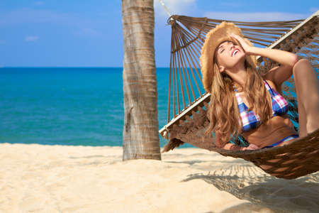 somnolent: Attractive woman in a bikini relaxing in a hammock with her face tilted back enjoying the sun on an idyllic tropical beach