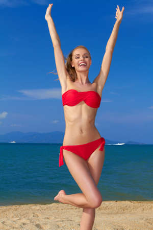 Joyful woman in red bikini with arms raised posing by the sea photo
