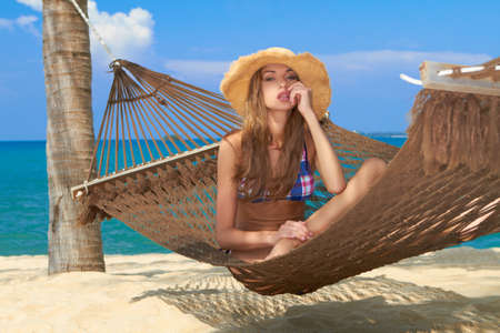 Beautiful cute girl relaxing in a hammock at tropical beach photo
