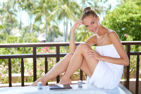 draped: Beautiful woman draped in a large white bath towel sitting on the rim of an open-air bathtub in the tropics Stock Photo