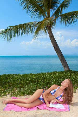 Beautiful blonde woman relaxing on a pink towel under a palm tree reading on a tropical beach with ocean backdrop photo