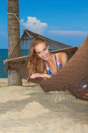 getaways: Sonriente mujer descansando en una hamaca en una playa disfrutando de una escapada tropical id�lica