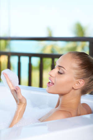 soaking: Beautiful blonde woman relaxing soaking in a bubble bath blows bubbles off her hand Stock Photo