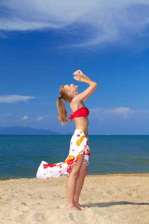 Joyful woman in red bikini with arms raised posing by the sea Stock Photo - 13345980