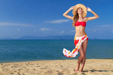 Girl wearing bikini and hat and posing at the sandy beach photo