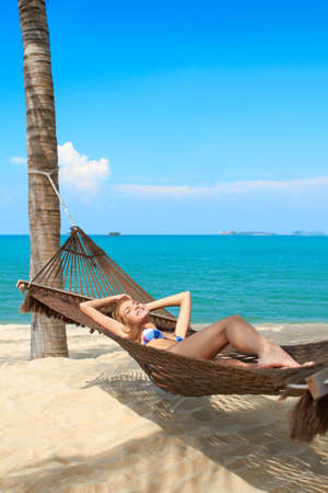 retreat: Woman tourist on a summer vacation enjoying the serenity of a tropical beach at a waterfront retreat