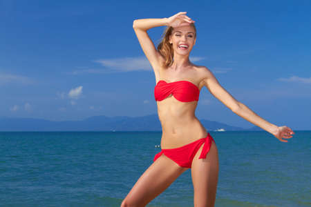 shapely: Beautiful laughing shapely woman on summer vacation posing in front of the ocean in her red bikini