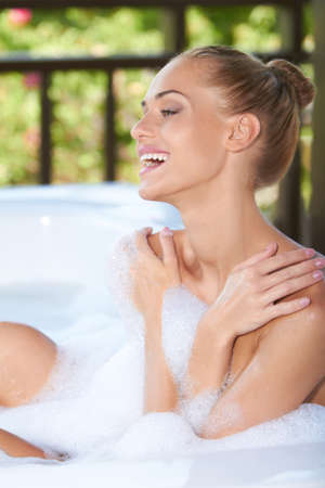 soaks: Vivacious blonde woman laughing in enjoyment as she soaks in the soapy bubbles of her bubble bath