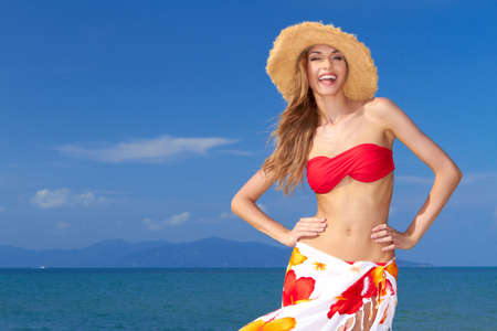 merriment: High-spirited beautiful woman laughing in merriment as she poses in front of the ocean in her bikini and colourful sarong