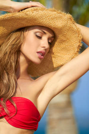 Sexy woman with arms raised wearing hat and red bikini photo