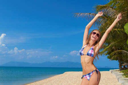 Attractive young woman in sunglasses joyfully raising her arms in celebration of the freedom of a beach vacation photo