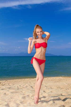 bikini slender: Beautiful female posing in red bikini on sandy beach by the sea