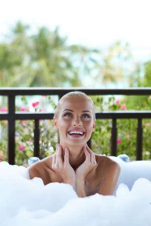bubble bath: Pretty smiling woman sitting enjoying a foamy bubble bath looking upwards off camera