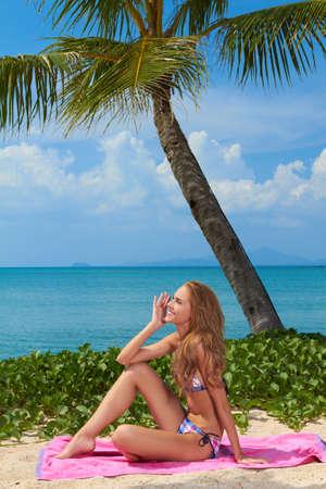 suntanning: Beautiful woman in a bikini sitting on a towel on a tropical beach Stock Photo