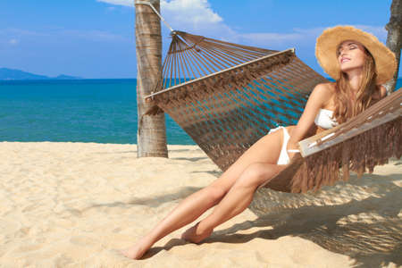 hamaca: Mujer elegante en bikini tumbada en una hamaca colgada entre palmeras en la playa de un centro turístico tropical