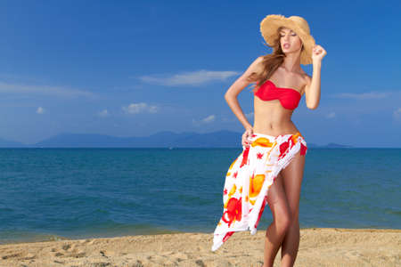 coy: Coy blonde beauty in a red bikini showing her beautiful legs and figure