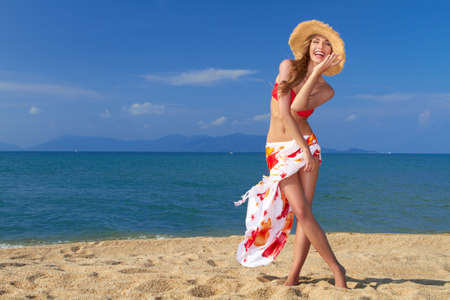 Smiling woman in straw hat with scarf around her waist posing on sandy beach by the sea Stock Photo - 13346045