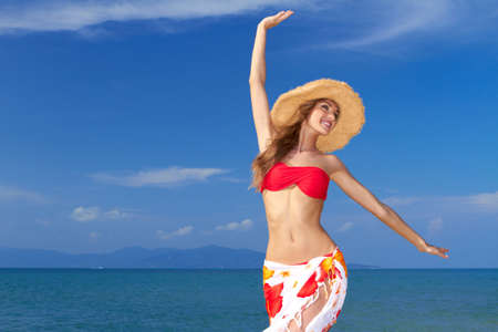 joys: Beautiful lively woman full of the joys of life twirling with her arms in the air in a colourful bikini and sarong against an ocean backdrop