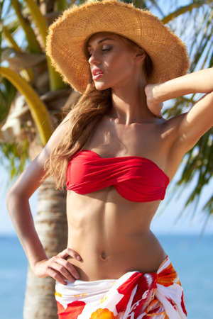 raised arms: Gorgeous bikini clad blonde in front of an oceanside palm tree
