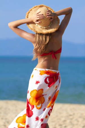 facing away: Woman in a colourful tropical sarong and straw hat standing on a beach facing away from the camera out over the ocean with her arms raised