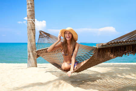 elan: Vivacious beautiful woman wearing a straw sunhat relaxing in a hammock tied to a palm tree on a tropical island resort