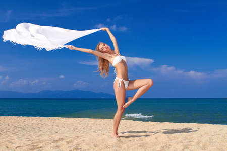Bikini clad blonde beauty in a dancers pose on soft white sand with the ocean in the background photo
