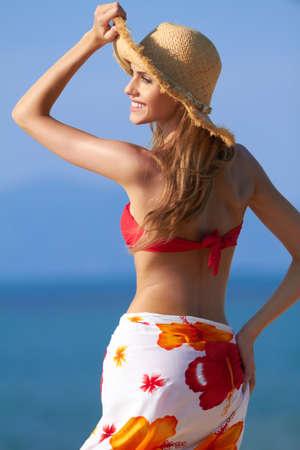 Lächelnden Blondine in einem roten Bikini und Sarong Wickelrock mit einem Hut als Sonnenschutz