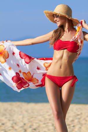 scarf beach: Hermosa rubia en un bikini rojo dejando que su flujo de pareo en la brisa en el oc�ano Foto de archivo