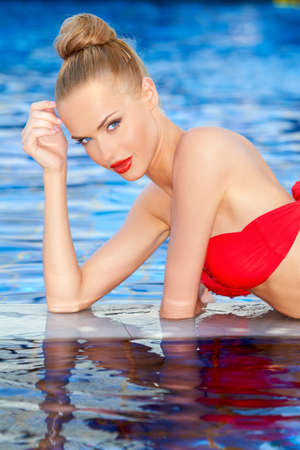 Beautiful blonde in a red bikini reclining by the pool checking you out as you pass by photo