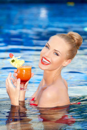 Pretty blonde girl with a big smile holding a tropical drink while standing in a swimming pool photo