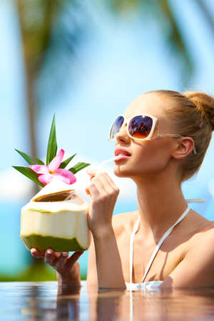 sipping: Woman soaking in a pool in her bikini and sunglasses sipping a tropical cocktail through a straw Stock Photo