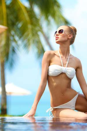 Woman in a bikini and sunglasses sitting on the rim of an infinity pool enjoying the tropical sun Banco de Imagens