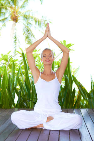 inhale: Beautiful smiling woman seated in the lotus position on a wooden deck amongst lush tropical plants doing yoga breathing exercises with her arms raised