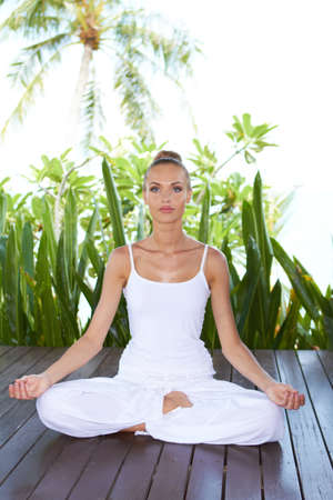 Beautiful serene woman meditating in the lotus position on a wooden deck with a backdrop of lush tropical vegetation Stock Photo - 13857648